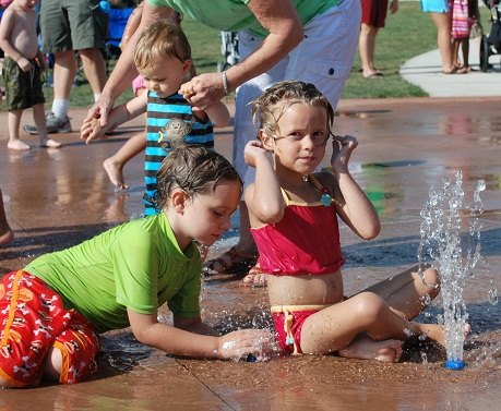 girl sitting and boy laying down in splashpad.JPG